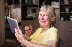 Cute senior woman using tablet computer Royalty Free Stock Photos