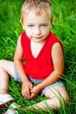Cute serene kid on fresh green grass. Portrait of cute serene kid on fresh green grass Stock Photo