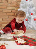 Cute serious baby girl in red dress making cookies for Christmas Stock Photos