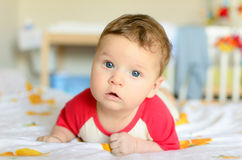 Cute serious baby lies on his tummy Royalty Free Stock Photo