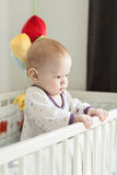 Cute serious baby standing up in a cot in child' Royalty Free Stock Photo