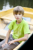 Cute serious boy sitting in boat Stock Image