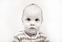 Cute serious child with eyes wide open looks strai Stock Image