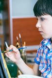 Cute, serious and focused, seven years old boy in blue shirt drawing on canvas standing on the easel. Concept of early. Childhood education, painting, talent royalty free stock image