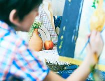 Cute, serious and focused, seven years old boy in blue shirt drawing on canvas standing on the easel. Concept of early. Childhood education, painting, talent royalty free stock images