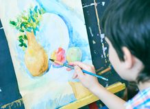 Cute, serious and focused, seven years old boy in blue shirt drawing on canvas standing on the easel. Concept of early. Childhood education, painting, talent stock image