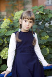Cute serious girl with plaits sitting. On fence nearby bush of hydrangea Stock Photo
