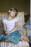 Cute serious girl sitting on chair stock photography
