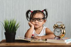 Cute serious looking little asian toddler wearing eyeglasses reading a book on a table. Concept of education, child development, growth and eye care stock photography