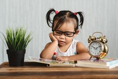 Cute serious looking little asian toddler wearing spectacle reading a book on a table. Concept of education, child development, growth and eye care stock photography