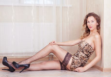 Cute woman lying on the floor stockings and leopard dress Royalty Free Stock Images
