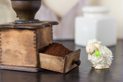 Cute sheep toy at coffee grinder. Cute fuzzy sheep toy with green flower sitting in front of open drawer of fresh coffee grounds in old manual grinder Royalty Free Stock Photos