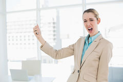 Cute shocked businesswoman holding her smartphone looking at camera Stock Photography