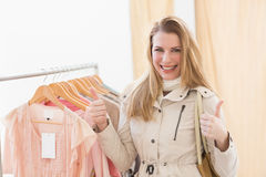 Cute shopping blonde smiling at the camera with thumbs up Royalty Free Stock Images