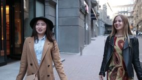 Cute shopping women walking with bags on street. Attractive teenage girlfriends walking with shopping bags on the street, looking happy. Stylish asian woman in stock video