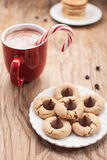 Cute shot of Christmas cookies and hot chocolate. Plate of snickerdoodle cookies, hot chocolate, peppermint candy cane, and chocolate peanut blossom cookies on Stock Photo
