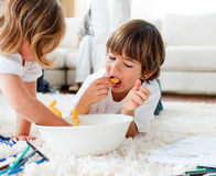 Cute sibling eating french fries on the floor. At home Royalty Free Stock Images