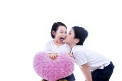 Cute sibling with heart pillow - isolated Stock Photography