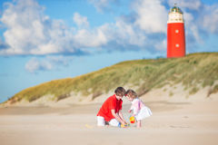 Cute siblings on the beach next to lighthouse Royalty Free Stock Images