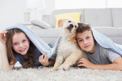 Cute siblings with dog under blanket in living room Royalty Free Stock Photos