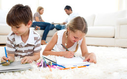Cute siblings drawing lying on the floor Stock Photography