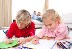 Cute siblings drawing lying on the floor Royalty Free Stock Photography