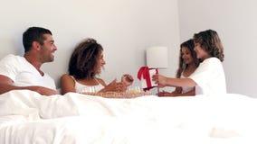 Cute siblings giving breakfast to their parents having breakfast. In bed in slow motion stock footage