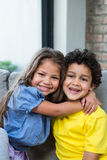 Cute siblings hugging on the sofa Stock Photography