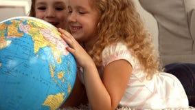 Cute siblings looking at globe stock footage