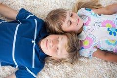 Cute siblings lying on the floor Stock Photos