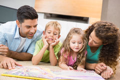 Cute siblings lying on the rug reading storybook with their parents Royalty Free Stock Images