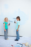 Cute siblings painting a wall Stock Images