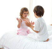 Cute siblings playing on the bed Royalty Free Stock Photography