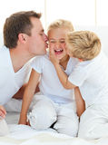 Cute siblings playing with their father Stock Photography