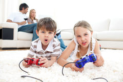 Cute siblings playing video games. Lying on the floor Stock Photography