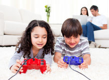 Cute siblings playing video games. Laying down on the floor in the living room Stock Photo