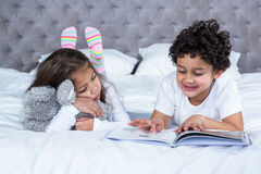 Cute siblings reading a book on the bed Stock Photo