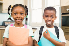 Cute siblings ready for school. Looking at the camera in the kitchen Royalty Free Stock Photography