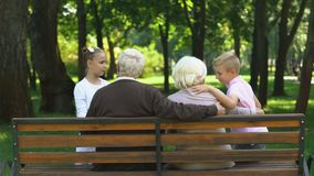 Cute siblings running to grandparents sitting on bench in public park, family. Stock footage stock video