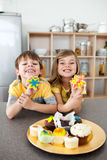 Cute siblings showing their cookies Stock Photos