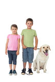 Cute siblings smiling at camera with their labrador dog Stock Photos