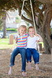 Cute siblings swinging. In a park Stock Photos