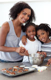 Cute siblings with their mother making biscuits Royalty Free Stock Image