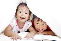 Cute siblings under blanket. Cute asian siblings reading book under blanket. shot in studio Royalty Free Stock Photo