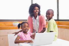 Cute siblings using laptop together with mother Royalty Free Stock Image