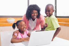 Cute siblings using laptop together with mother Royalty Free Stock Photos