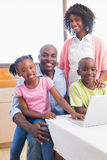 Cute siblings using laptop together with parents Royalty Free Stock Image