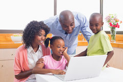 Cute siblings using laptop together with parents Stock Photos