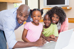 Cute siblings using laptop together with parents Stock Photography