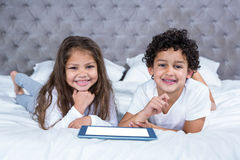 Cute siblings using tablet on the bed Royalty Free Stock Images